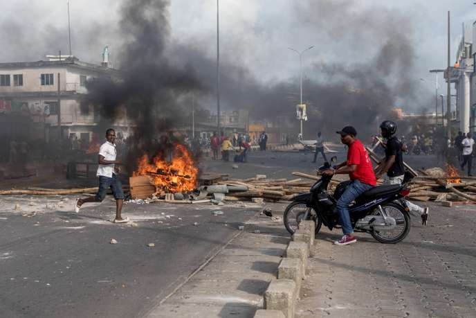 Demonstrator are seen as smoke rises from barricades during a protest in the streets of Cadjehoun, district of former president of Benin Thomas Boni Yayi, as demonstrators gather on May 1, 2019 in Cotonou. - Protestors in Benin set up burning barricades on the streets on May 1, as soldiers encircled the home of ex-president Thomas Boni Yayi after he led calls for an election boycott. Hours after initial results showed a record low turnout in Sunday's controversial parliamentary polls, soldiers in tanks were posted on the main roads leading to Boni Yayi's home in the economic capital Cotonou. (Photo by Yanick Folly / AFP)