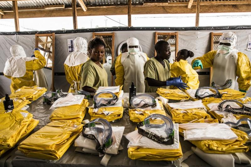Des agents de santé revêtent leur équipement de protection individuelle avant d'entrer dans la zone où les personnes potentiellement atteintes du virus Ebola sont placées en quarantaine pour être suivies et traitées (janvier 2019)