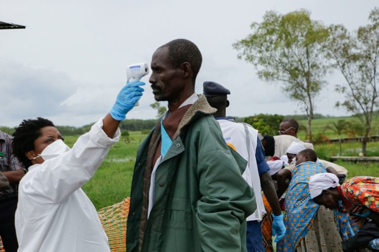 A medical staff member measures a man's temperature as a preventive measure against the COVID-19 coronavirus on his arrival of repatriation in Gatumba, on border with the Democratic Republic of Congo (DRC), in Burundi, on March 18, 2020. (Photo by ONESPHORE NIBIGIRA / AFP)